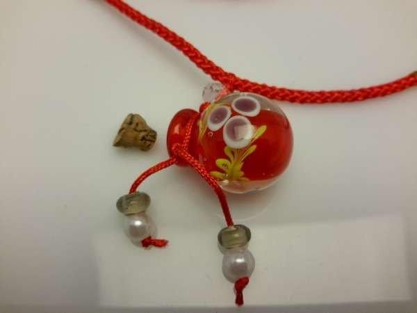 Touwketting, rood, hanger: rood bolvormig muranoflesje, facetkraal en diverse kralen