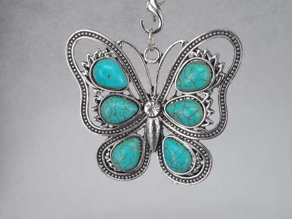 Hanger vlinder met strass en turquoise steentjes.