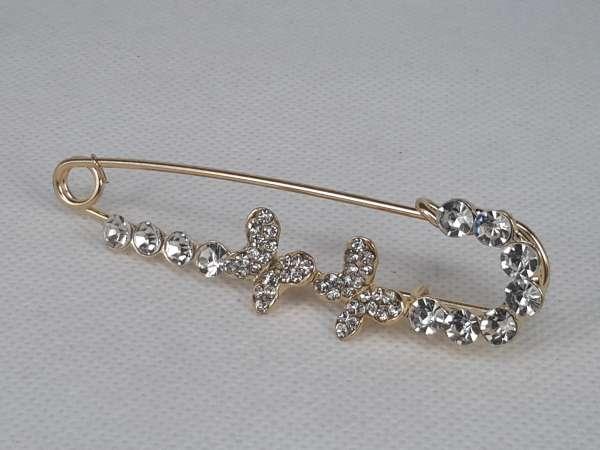 Speld, goudkleurig metaal, langwerpig, strass op een pin met 2 kleine vlinder op de ronding.