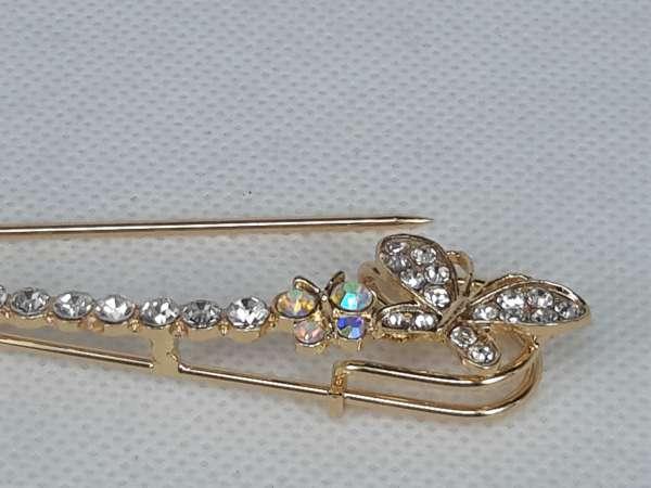Speld, goudkleurig metaal, langwerpig, strass op een pin en op grote en kleine vlinder op de ronding.