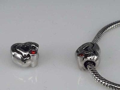 Zilverkleurige pandora style bedel: hartje met zwarte lijnen en rood oogje