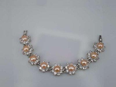 Armband, zilverkleur, 9 zoetwaterparels omgeven met glassteen, rosé of zalm